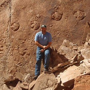 vince standing at large fossil trackway
