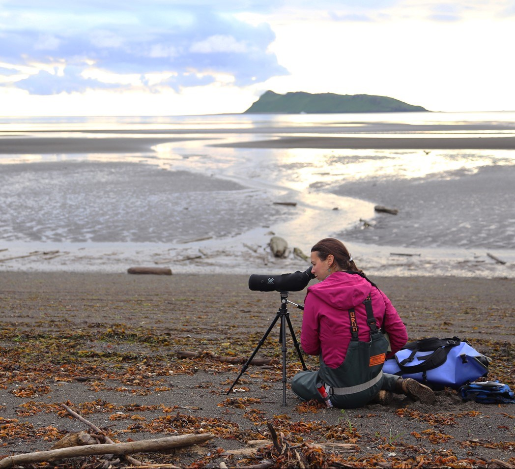 Scientist making observations with telescope on beach.