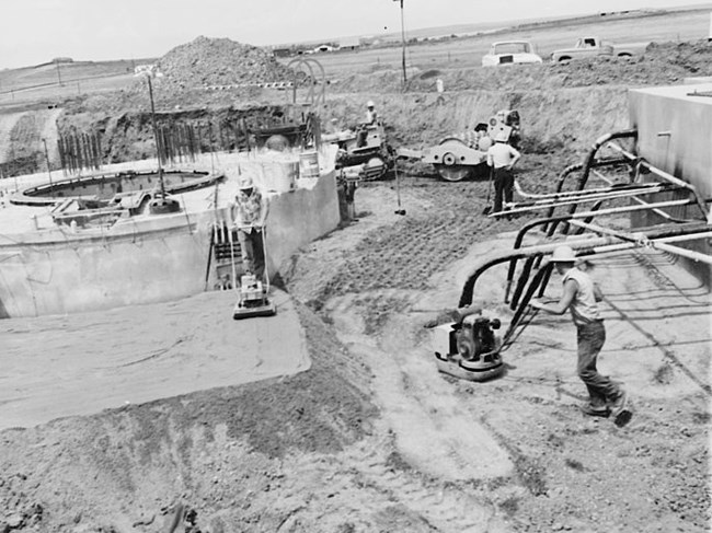 men work at a site with concrete features