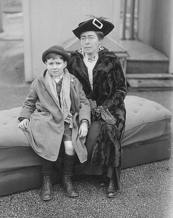 A woman in black sits next to a boy wearing a suit