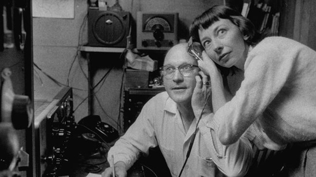 A man and woman share a radio headset