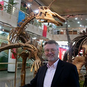 scientist in museum hall with dinosaur skeleton