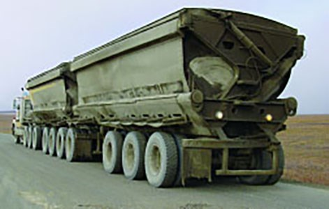 Semi-truck with two trailers hauling ore on a dusty, gravel road.