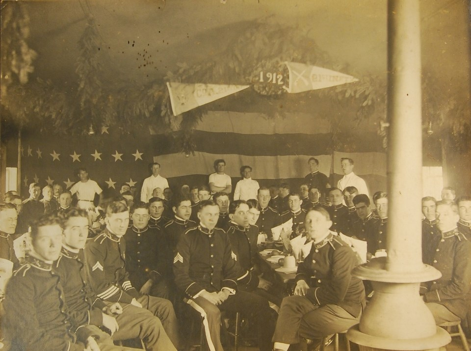 Photo of group of seated soldiers indoors. Behind them is a large American flag. Hanging above is Christmas greenery and banners that say 1912 and 21st Infantry.