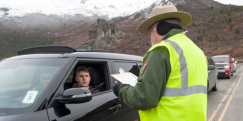 A park rangers talks to visitors in a car
