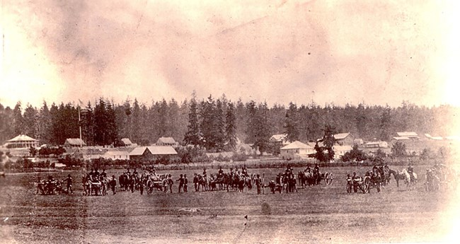 Soldiers, horses and cannons stand in a field. Behind them are barracks buildings.