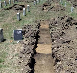 Shallow trenches dug between rows of graves.