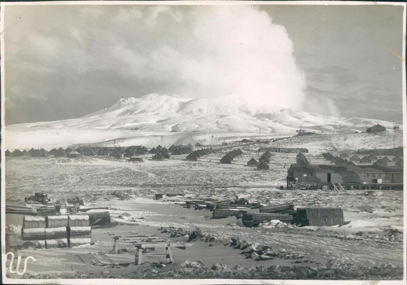Black and white photo of small tents and buildings with snowy mountain in background.