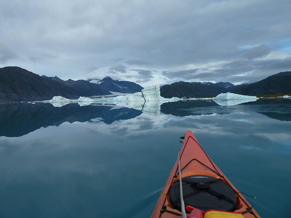 A kayak noses through a lake with icebergs and a glacier and mountains in the background.