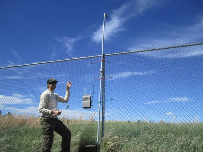 Man in front of a fence with monitoring equipment attached to it