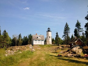Front view of lighthouse and keeper's house after treatment. Vegetation and trees have been cleared from the area surrounding the buildings.