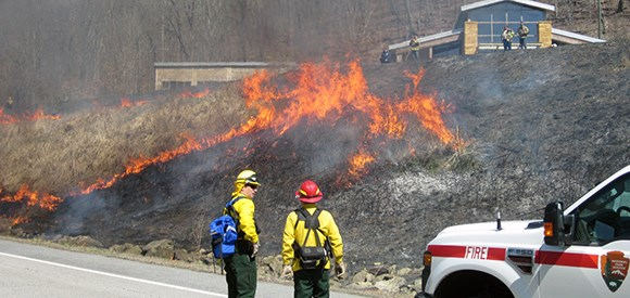 Two firefighters stand on a road as fire moves up a grassy slope toward the visitor center.