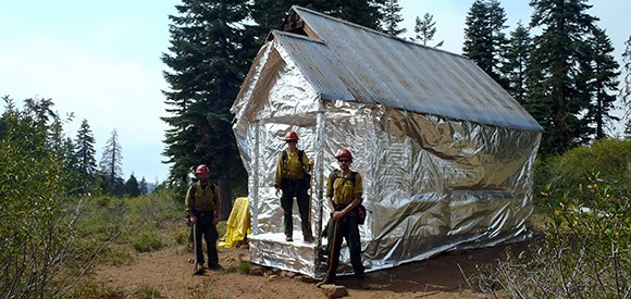 Firefighters stand near a cabin wrapped to protect it from wildfire.