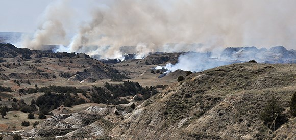 Smoke rises in multiple places from badlands.