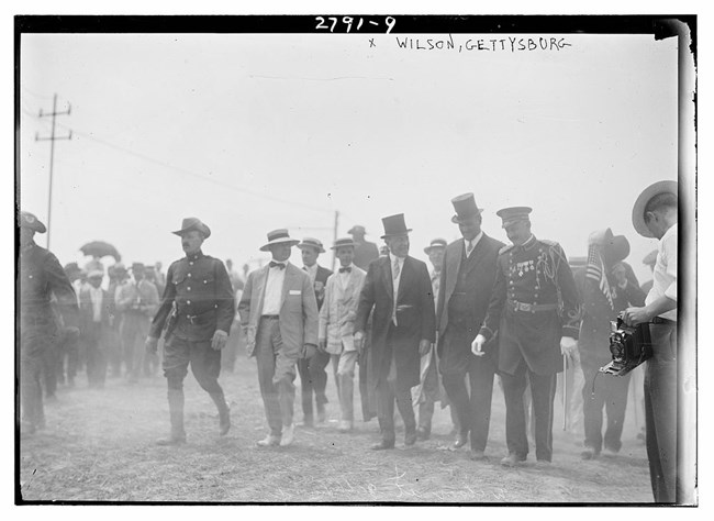 Several men walking side by side. Two men wear top hats and two are in uniform.