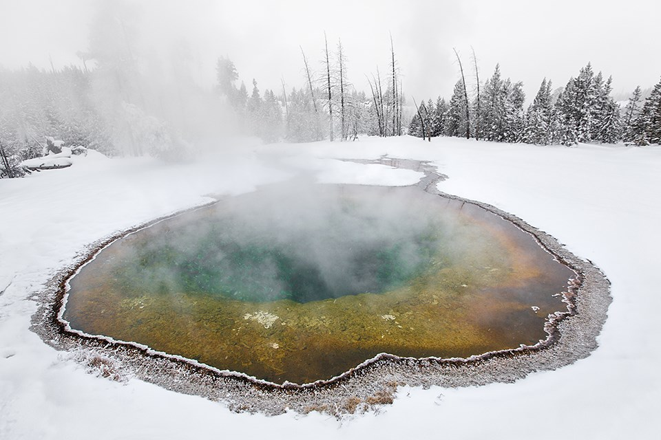 A colorful thermal pool surrounded by white snow