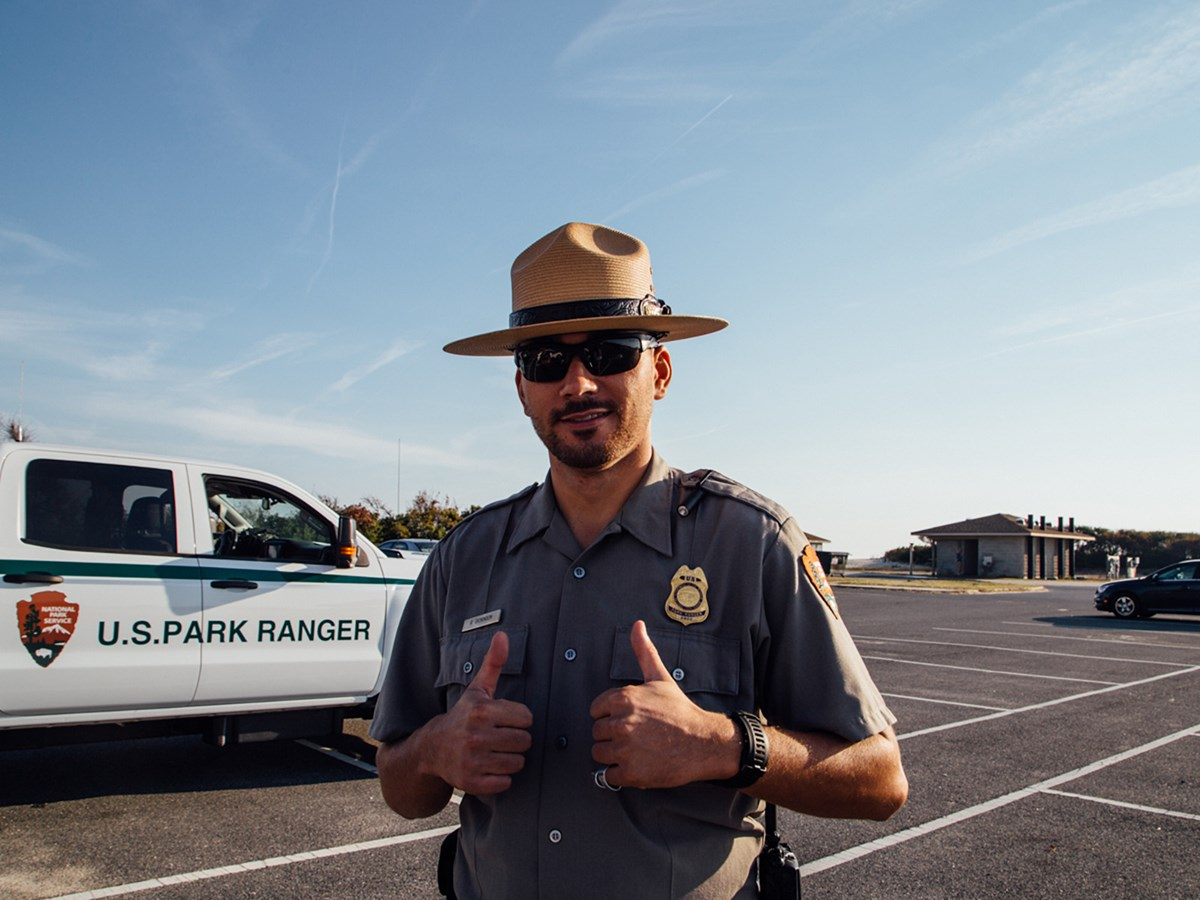 photo of Law Enforcement Ranger in front of National Park Service vehicle giving two thumbs up