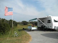 Campsite with RV, picnic table, chairs and American flag, 33kb.