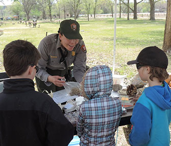Park ranger and kids looking at seeds.