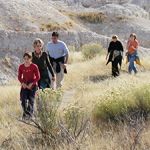 Five people hike through grassland with badlands formations in the background