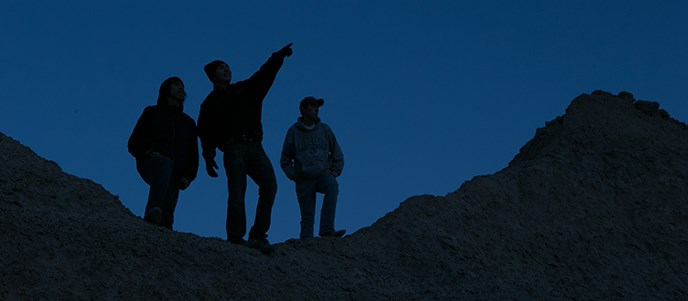 three Youth Camp participants stand atop the badlands formations, silhouetted against a twilight sky