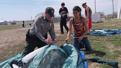 ranger and student pitch a tent