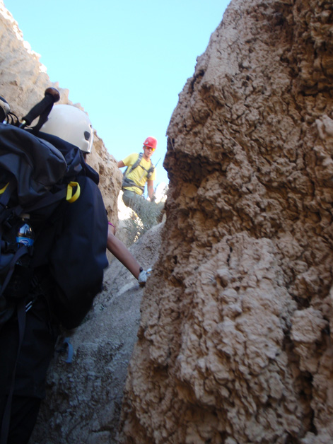 Search and Rescue team members climb through rugged badlands terrain.