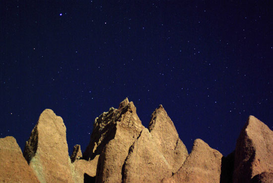 Badlands formations against the night sky with stars.