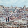 watercolor painting of an adult and child walking among the badlands formations - by Judy Thompson