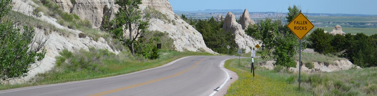 a road winds between badlands formations with a yellow sign on the right that says fallen rocks.