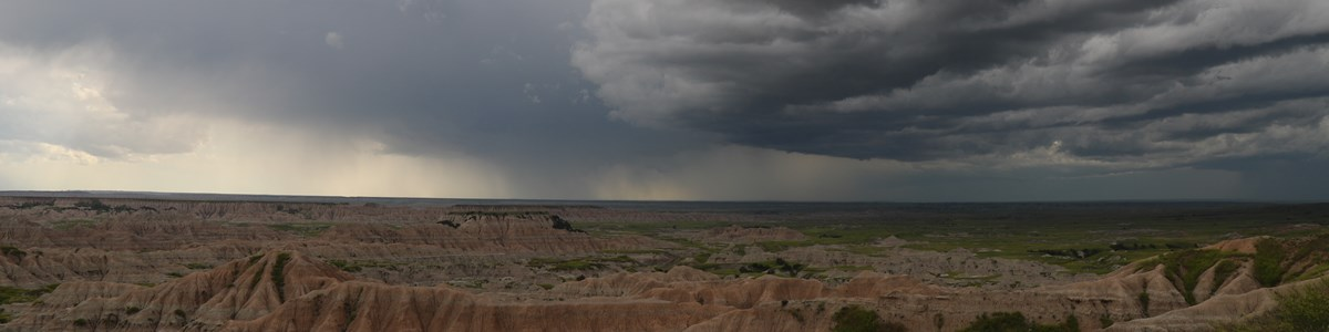 dark storm clouds and distant rain roll over sprawling badlands formations.