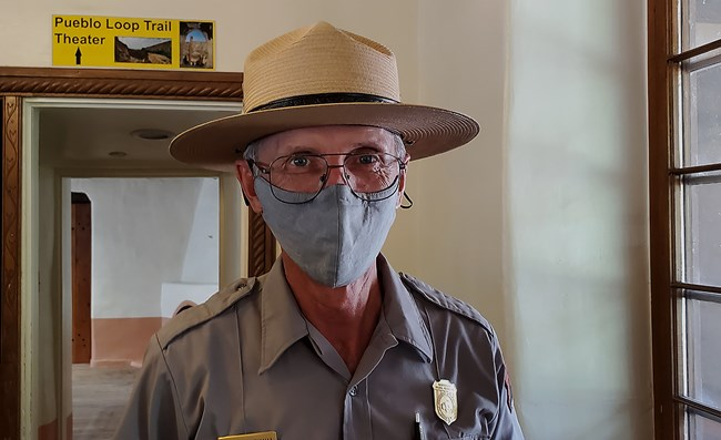 a man wears a mask and a ranger hat