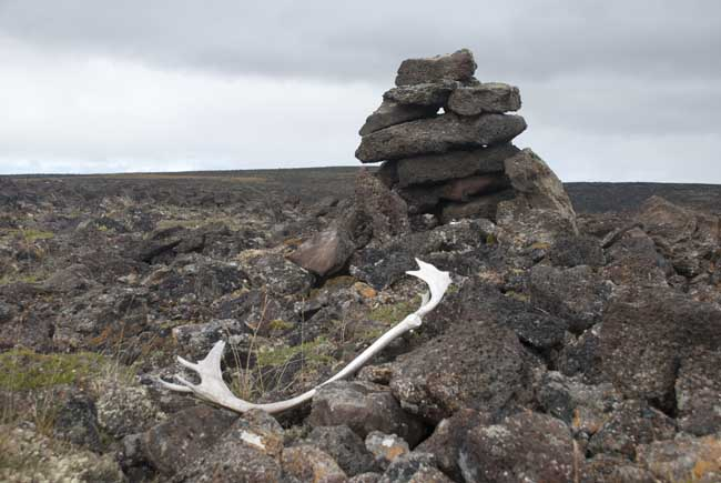 A caribou antler sits in front of a stone structure, with cloudy skies in the background