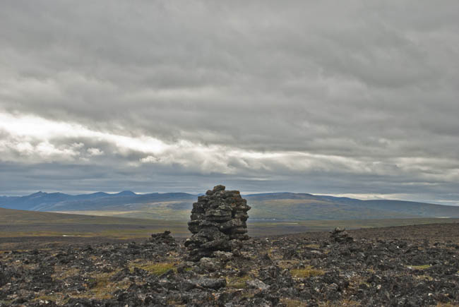 Stormy skies boil dramatically behind ancient stone structures on the caldera rim