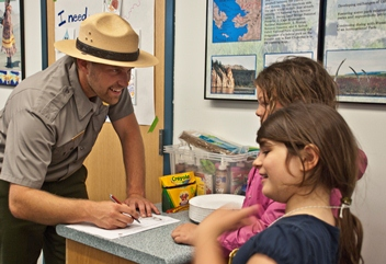 A park ranger smiling at two students as he signs a Junior Ranger certificate