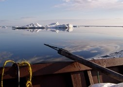 A seal hunting harpoon rests on the side of a wooden boat, looking out on a glassy sea with sea ice on the horizon