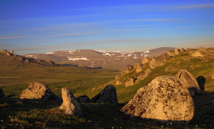 A view of the granite tors in Hot Springs Valley in vivid sunset colors, with green tundra, and patches of snow on distant mountains.