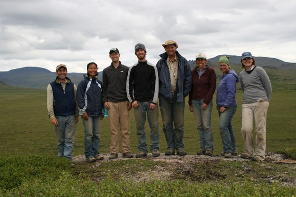 An excavation crew of 8 men and women stands in a row on the tundra, smiling.
