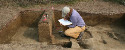 Archeologist Kelly Graf documenting a stratigraphic profile, kneeling in a square pit carved out from the ground.