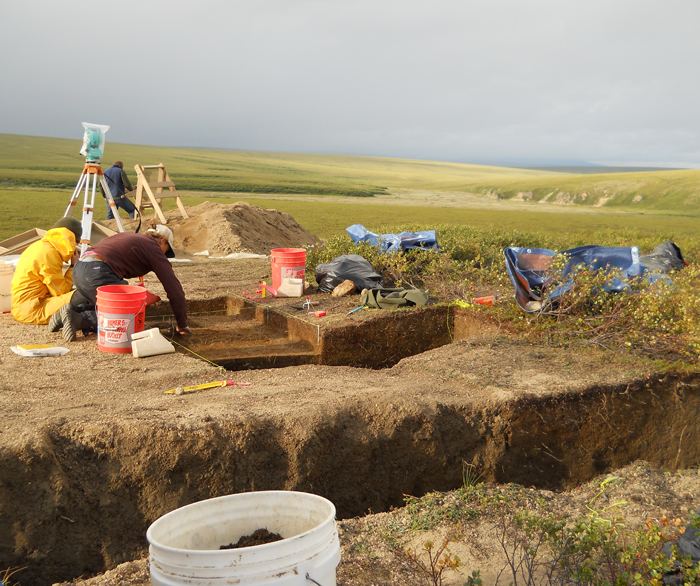 Two archaeologists dig out an excavation site on the tundra under a gray sky