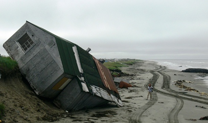 A house that has fallen off an eroded shoreline onto the beach in Shishmaref