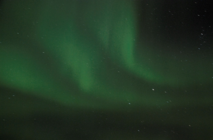 Three ribbons of green northern lights sweep across the night sky