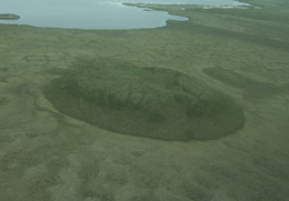 An aerial view of a large round pingo, with a pond in the distance