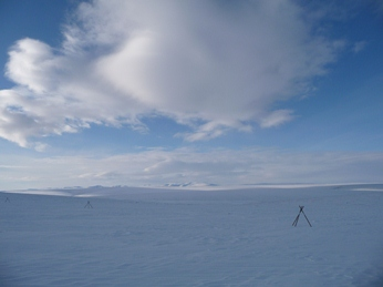 A flat, snow covered tundra with snowmobile tripod markers, under blue sky with clouds