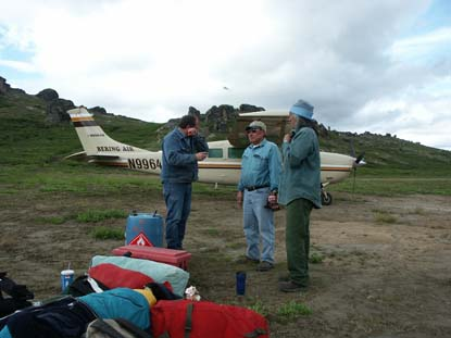 Three men with camping gear standing near a small airplane