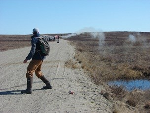 A person stands on a dirt road, spraying bear mace out to the side, demonstrating proper use.