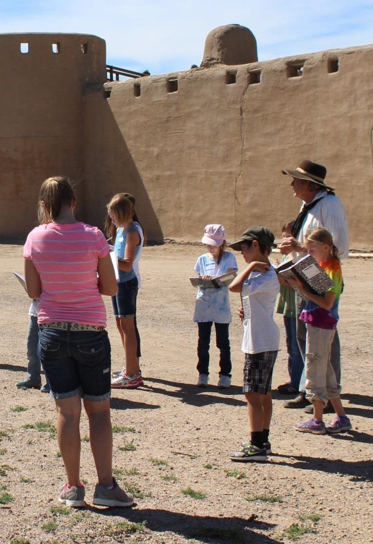 Children writing in journals with a living historian in front of Bent's Old Fort.