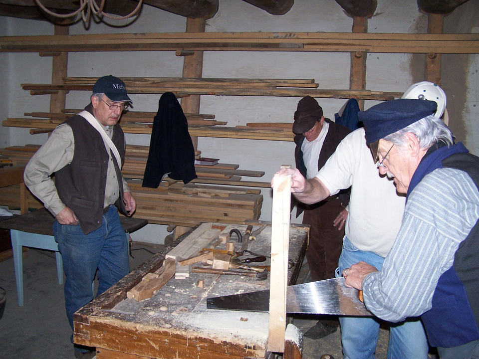 Carpenters building a milking stool.