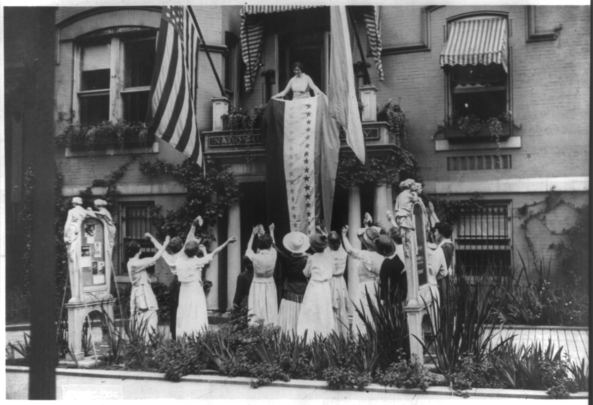 Alice Paul hangs a large tricolored banner from the balcony of the National Woman's Party headquarters. A dozen suffragists cheer on the ground below.