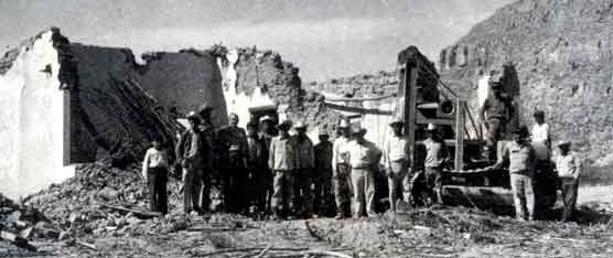 Men standing in front of the ruins of Chata's restaurant, 1957.